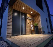 Petite terrasse d'entrée avec éclairage extérieur.