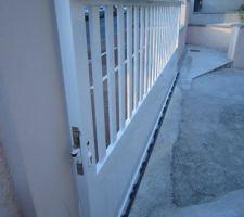 Le portail est en place sur le rail. Reste la gâche à fixer sur le pilier.