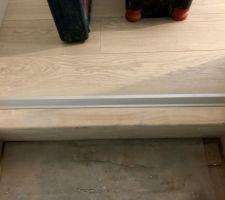 Barre de rattrapage de niveau posée entre le parquet et l'escalier
