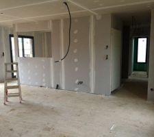 Salon/séjour vue sur cuisine semi-ouverte avec la découpe prévue pour la verrière d'atelier (à gauche) et dégagement entrée avec à gauche porte WC et au fond SDE zone vie.