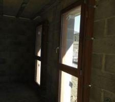 """Les 2 fenêtres avec allèges vitrées de la cuisine. Gamme Lena 56 classic de chez MOLENAT. Essence bois exotique: niangon. La teinte du bois est plutôt jolie. Par contre dommage pour la quincaillerie grise qui n'est pas tellement de mon goût. Des options plus """"rustiques"""" existent chez le fabricant mais je ne suis pas certain qu'elles s'appliquent aux châssis oscillo-battants et on en a pas parlé avec le constructeur."""