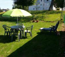 Petit salon de jardin dans la verdure.