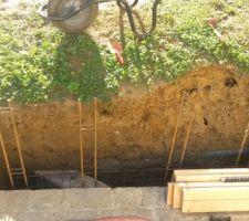 Mis en place des fers à béton verticaux pour le chaînage dans les blocs à bancher.