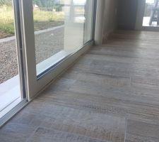 La baie à galandage est bien à niveau par rapport au sol de la pièce à vivre. En face accès PMR qui donne sur la terrasse couverte.