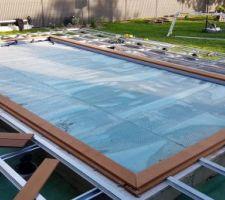 Démarrage de la terrasse autour de la piscine et en prolongement de la maison. Structure en acier. Ici, création des margelles avec les premières lattes pour tout bien mettre à niveau