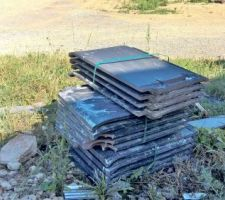 Tas de tuiles salies et cassées abandonné sur le devant de la maison.