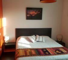 APRES : Chambre orange aux couleurs du Pérou dans laquelle nous avons déplacé le lit pour gagner de la place et fait une tête de lit avec des lames de parquet restantes collées sur une planche. Bordure de la tête de lit faite avec des baguettes d'angle peintes en noir.