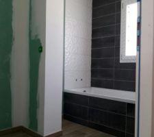 La salle de bain. Carrelage imitation parquet et faïence baignoire.