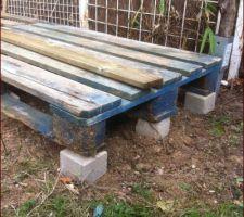 Abri bois : palettes posées sur des pavés
