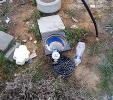 Compteur d'eau sorti de son logement (isolation à gauche, couvercle dessous) + bouteille d'eau
