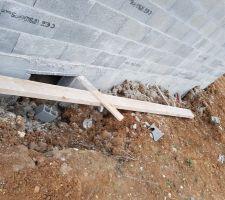 Planche de soutien des pignons abandonnée au sol avec serre-joint et morceaux de parpaing