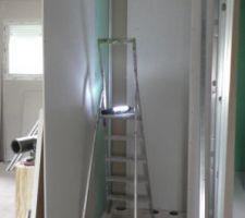 La préparation du perçage du plafond dans le WC. La zone est éclairée.