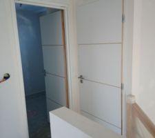 Porte des toilettes à droite, porte de la salle d'eau à gauche