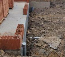 Remblaiement des fouilles autour de la maison après pose des drains.