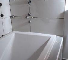 Pose de la faïence et de la mosaïque autour de la baignoire de la salle de bain