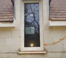 Menuiseries en triple vitrage. Porte fenêtre d'une chambre (en haut à gauche de la porte la barre en fer n'est pas bien plaquée, il y a un trou entre le mur et la barre).