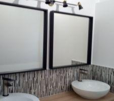 Les miroirs et luminaires sont installés dans la salle d'eau