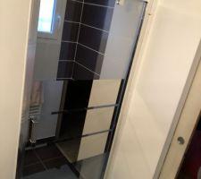 Mise en place de la nouvelle porte de douche dans la suite parental Porte semi-pivotante effet miroir