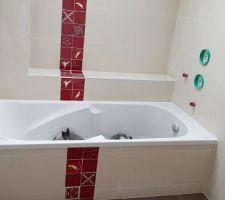 Salle de bain des enfants, avec une frise en carreau mexicain sur la baignoire.