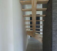 Escalier en pin lamellé-collé sur limon central. Première volée asymétrique, marches plus longues côté droit pour venir y faire reposer un claustra ultérieurement. Posé avec 2 cales provisoires sous la 1ère marche.