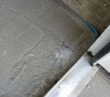 Un morceau de plastique pris dans la dalle. Malin d'avoir laissé le plastique sur la porte au moment du coulage de la dalle...