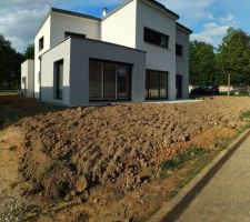 Aménagement du terrain avec le gravier en protection drainante des murs, et apport de terre végétale