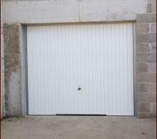 Porte de garage contractuelle qu'on aimerait changer pour une sectionnelle motorisée.