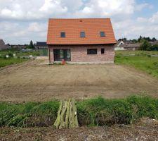 Vue sur l'arrière de la maison et du jardin plat vu depuis le talus