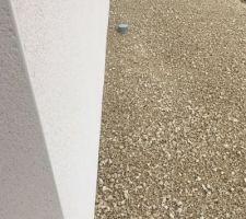 Chemin fait devant la maison avec un gravier blanc.