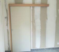 Nous avons choisi d'avoir une porte apparente coulissante pour aller dans le couloir des chambres. Nous allons changer la porte pour en mettre une avec du vieux bois.