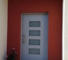 Façade avec crépis et la porte d'entrée large, lourde et épaisse.