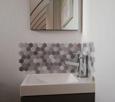 Pose d'un sticker façon mosaïque au dessus du lave main des toilettes