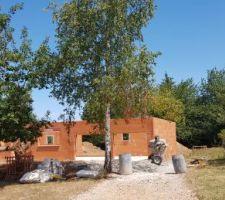 Fin de l'élévation des murs avec finitions, maison vue depuis le chemin d'accès.