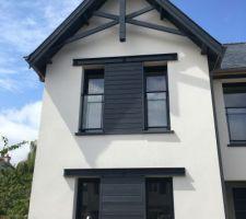 Détail de la façade avec éléments décoratifs en bois, bardage et UPN en métal