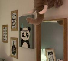 Trophée peluche éléphant et mur de cadres dans la chambre de notre bébé