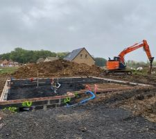 Préparation avant que la dalle soit coulée  Terrain remblayé, remise de terre autour des fondations maison, passage des gaines électriques et tuyaux d'évacuation