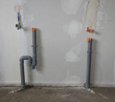 La chape ciment est coulée, les évacuations machine à laver et évier du cellier dépassent.