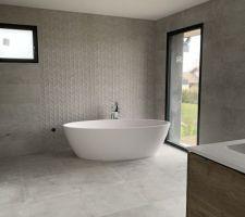 Voici notre salle de bain enfin terminée. Le carrelage est minéral dans sa couleur et au toucher. Une commode ancienne en bois, une plante et un tapis et elle sera parfaite.