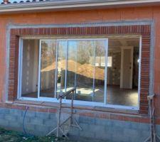 Briques de parement en cours de pose sur la baie vitrée