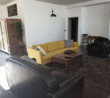 Coin salon avec nouveau canapé jaune BoConcept et tapis moelleux Ikea, meuble ancien frigo sur la gauche rénové en cave à vin (non réfrigérée)