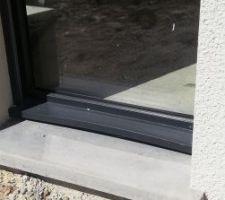 Photo porte fenêtre.  Problème de fabrication (appuie de fenêtre gondolé)