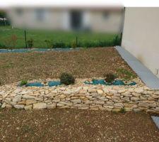 Muret en pierres sèches végétalisé pour habiller pente de terre. Fini !