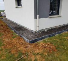 Pose de nos bordures pour chemin de propreté autour de la maison (remplissage en crasse avant cailloux bleus)
