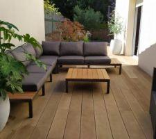 Evolution du coin détente avec un salon de jardin d'angle et quelques plantes en pot