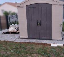 Pose dalles béton sur le côté de l'abris de jardin