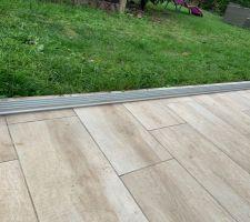 Détail du profilé au sol permettant de recevoir les vitres. Etanchéité au silicone transparent en dessous, des cales permettent de rattraper la planéité de la terrasse.