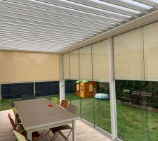 Vue stores partiellement baissés depuis l'intérieur. Si on ferme les côtés et qu'on laisse les vitres en façade, on est protégé de la pluie, de l'air et on conserve la lumière :)