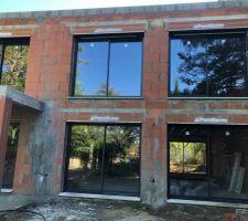 La façade est en brique Les baies vitrées sont faites au Pantone de notre choix avec volet électrique