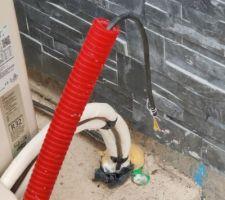 Gaine rouge avec câble électrique qui est relié à la pompe qui ensuite doit être relié au tableau