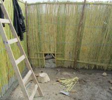 Fabrication d'un poulailler en roseau; dalle en pierre et ciment au sol. le toit sera en pointe (pour la pluie) et l'intérieur doit être plâtrée. les séparations intérieures sont en cours. poules, paon, canards, dindes. 4 séparations